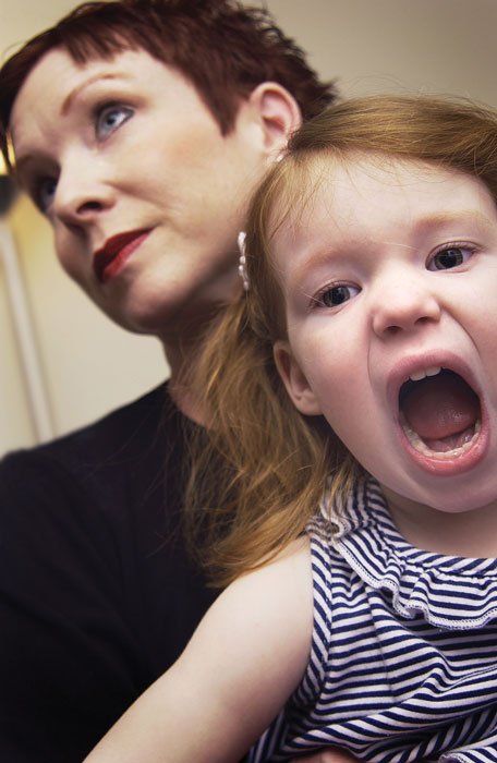 A photo shows a little girl screaming while a woman behind her looks away.
